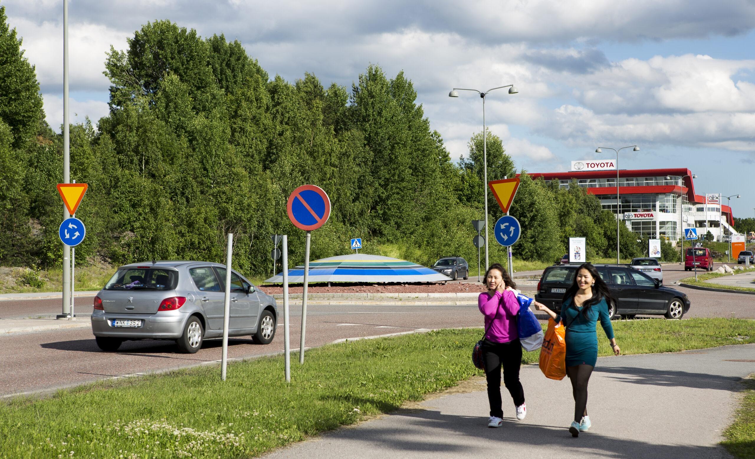 Två personer som går på trottoar med kassar och en bilväg med en bil.